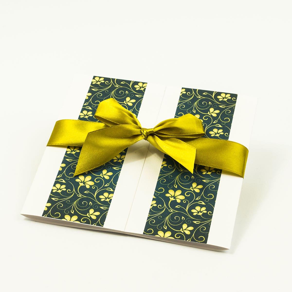 Zaproszenia ślubne z żółto-zielonym motywem kwiatowym, przewiązane wstążką po środku. ZAP-21-01