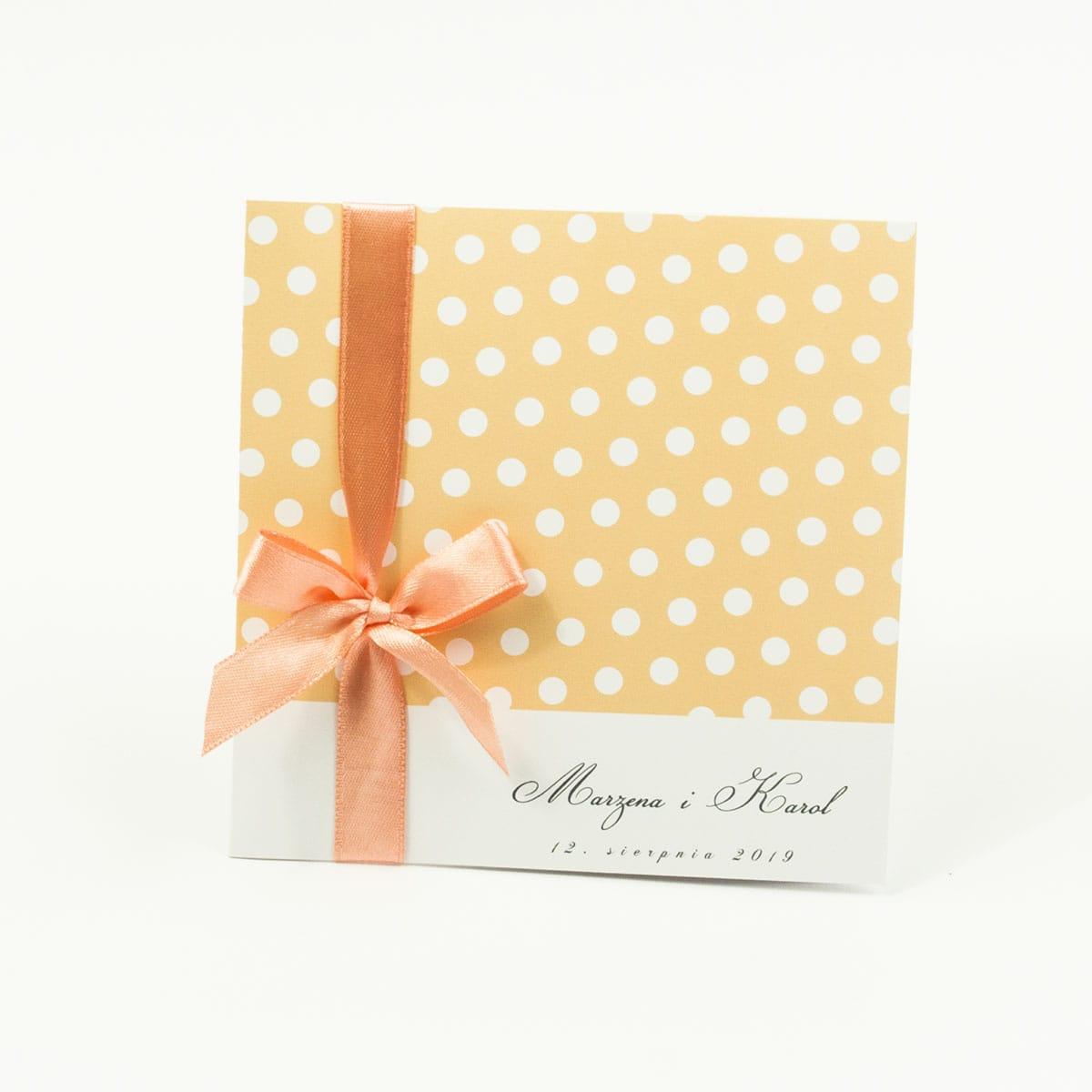 Urocze zaproszenia ślubne z białymi kropkami na brzoskwiniowym tle oraz brzoskwiniową wstążką. ZAP-81-01