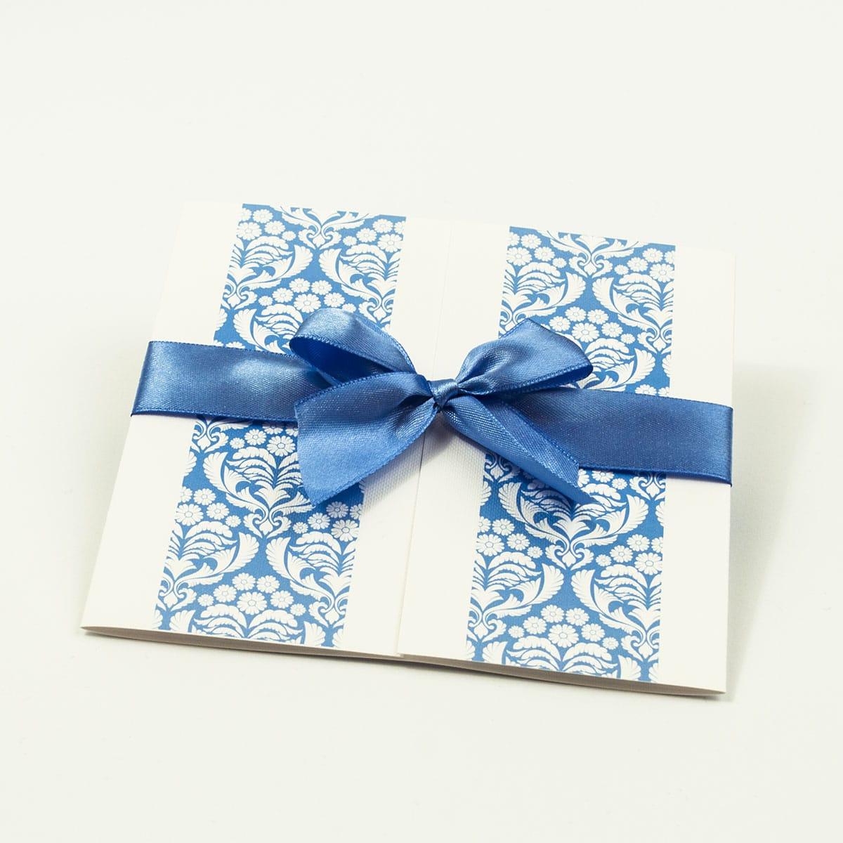 Zaproszenia z błękitno-białym ornamentem florystycznym, przewiązane wstążką po środku. ZAP-21-10