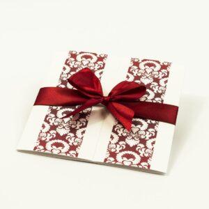 Zaproszenia z czerwono-białym ozdobnym ornamentem, przewiązane wstążką po środku. ZAP-21-11