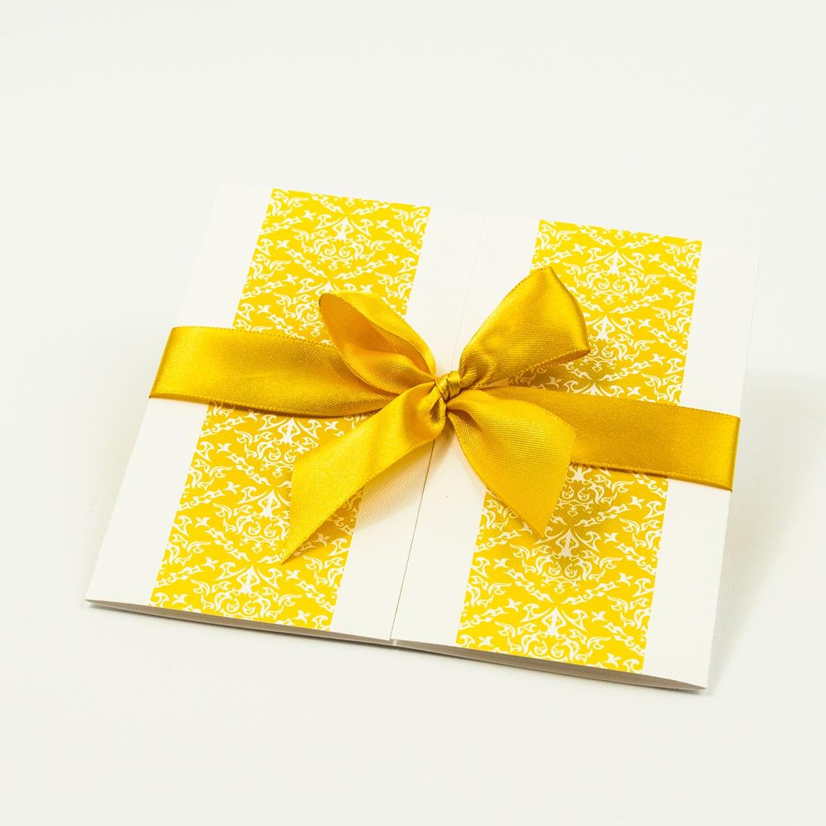 Zaproszenia z żółto-białą dekoracją, przewiązane wstążką po środku. ZAP-21-15