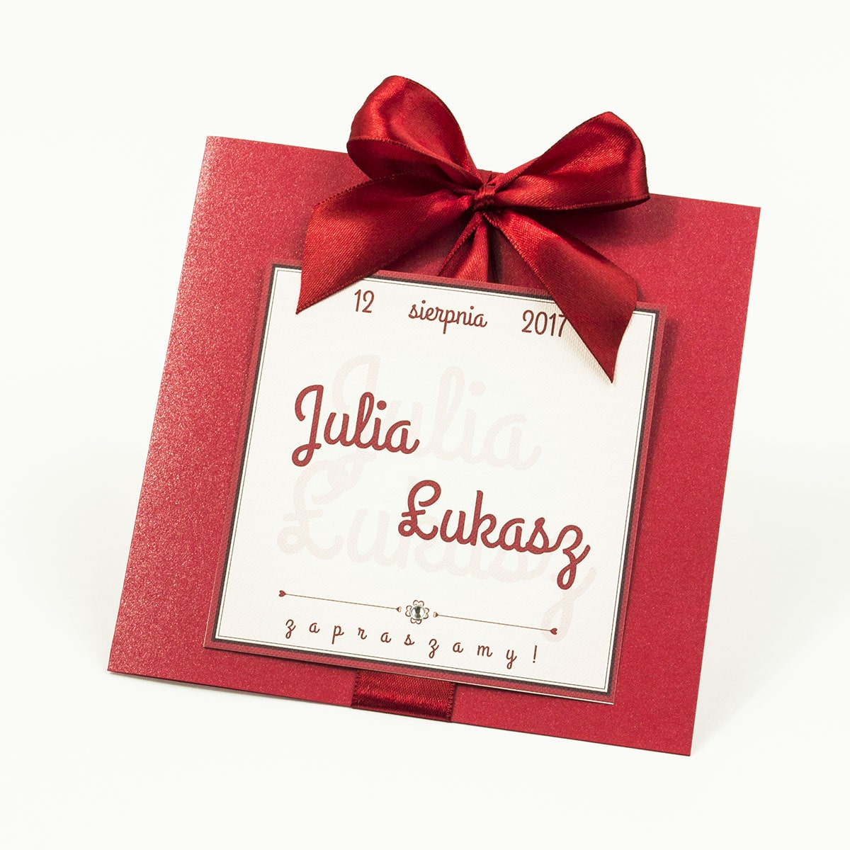 Zaproszenia ślubne na czerwonym papierze perłowym, ze wstążką w kolorze ciemnej czerwieni i cyrkonią oraz wklejanym wnętrzem. ZAP-61-80