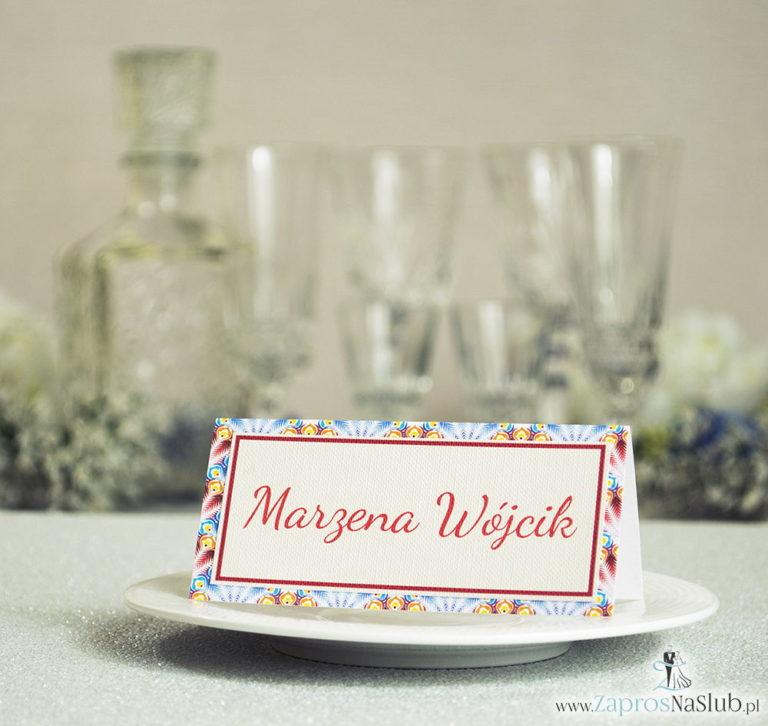 Eleganckie winietki ślubne z czerwonymi i niebieskimi piórami pawia, umieszczonym pod naklejonym motywem tekstowym - ZaprosNaSlub