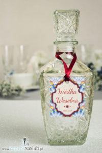 ZAW-2008 Zawieszki na alkohol z ornamentem. Eleganckie czerwone i niebieskie pawie pióra, wielobarwny motyw ozdobny oraz satynową wstążka - Zaproszenia ślubne na ślub