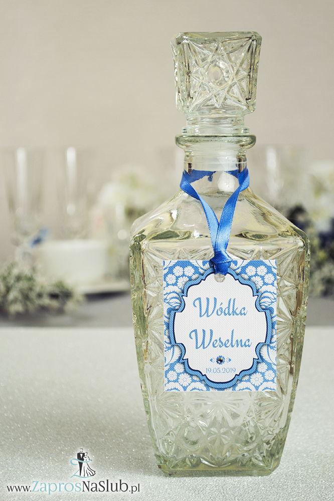 Zawieszki na alkohol z ornamentem. Elegancki błękitno-biały florystyczny wzór, trójbarwny motyw ozdobny oraz satynową wstążka