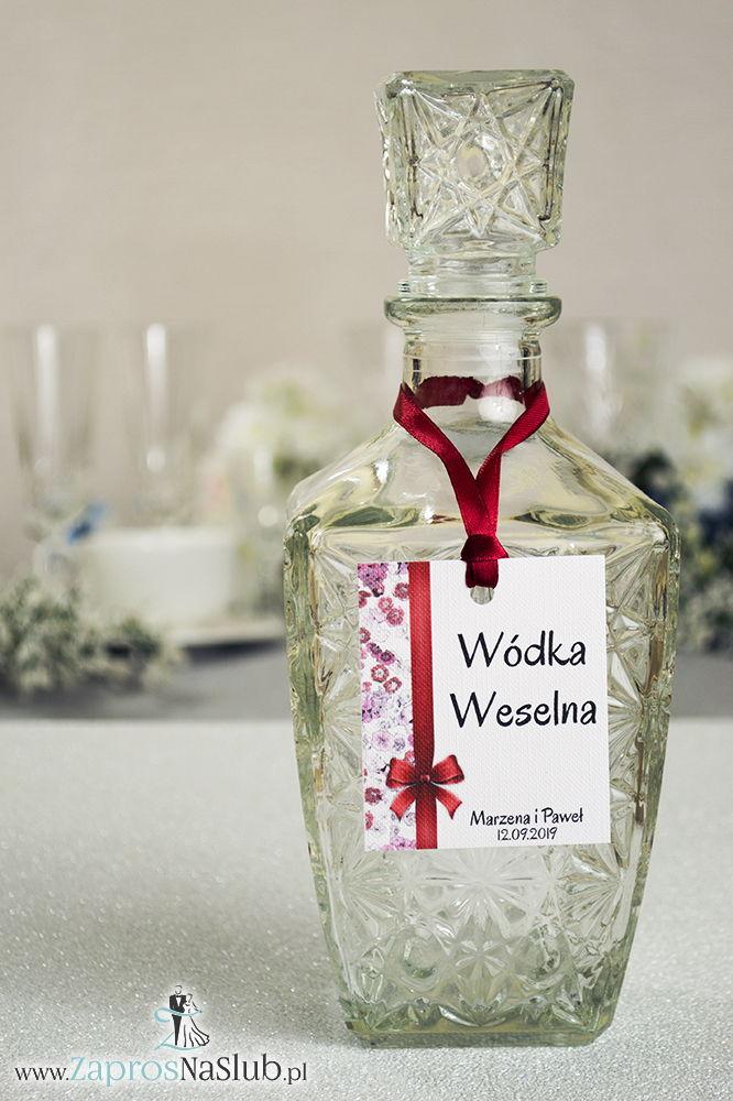 Kwiatowe zawieszki na alkohol wraz z ciemnoczerwoną wstążką i pionowym motywem kwiatów goździków - ZaprosNaSlub