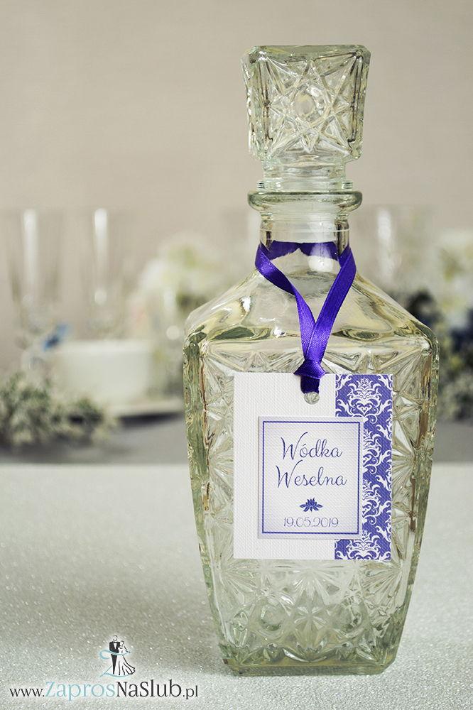 Zawieszki na alkohol z fioletowo-białym damaskiem po prawej, przyklejanym motywem tekstowym i fioletową wstążką