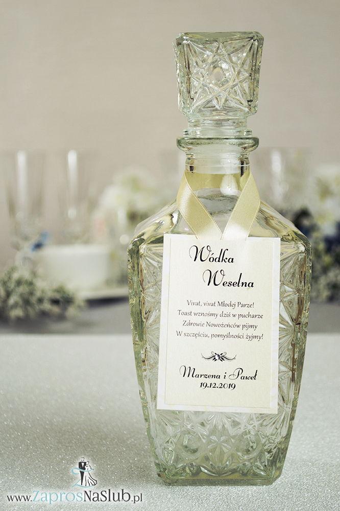 Bardzo eleganckie zawieszki na alkohol z papierem w kolorze biało-złotych róż, przyklejanym motywem tekstowym, cyrkonią i kremową wstążką
