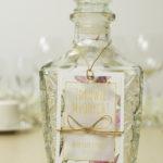 modne-zawieszki-na-alkohol-z-kwiatami-magnolii-złotym-sznurkiem-metalizowanym-i-złotą-kokardką