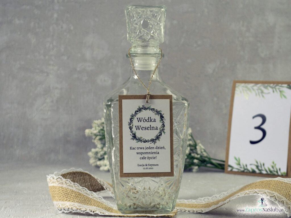 Zawieszka na butelkę eko w stylu rustykalnym z naklejanym białym papierem i wiankiem z zielonych liści ZAW-111-1